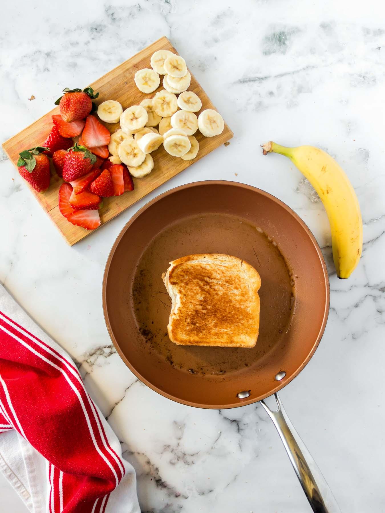 Grilling a peanut butter sandwich in a pan.