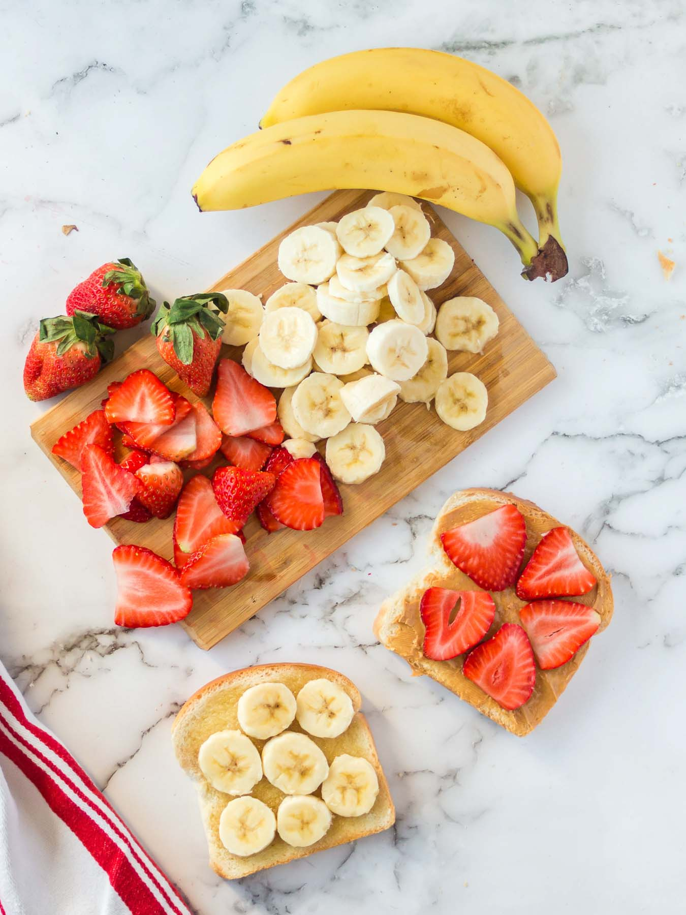 Peanut butter sandwich halves with banana slices and strawberry slices.