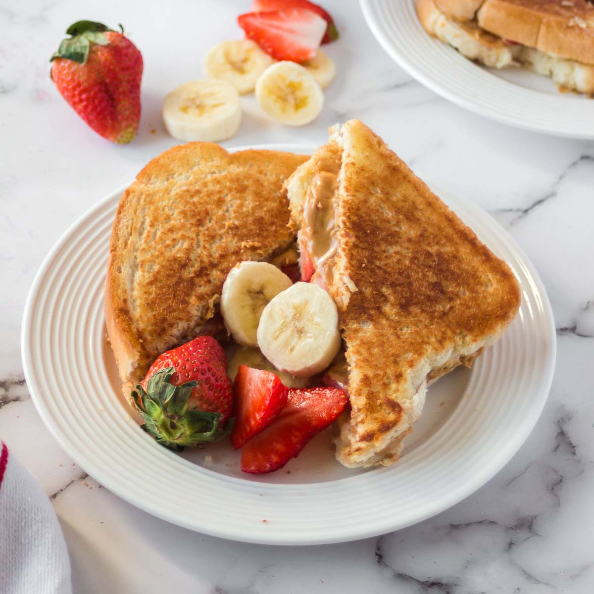 Grilled peanut butter sandwich sliced on a plate with fresh strawberries and banana.
