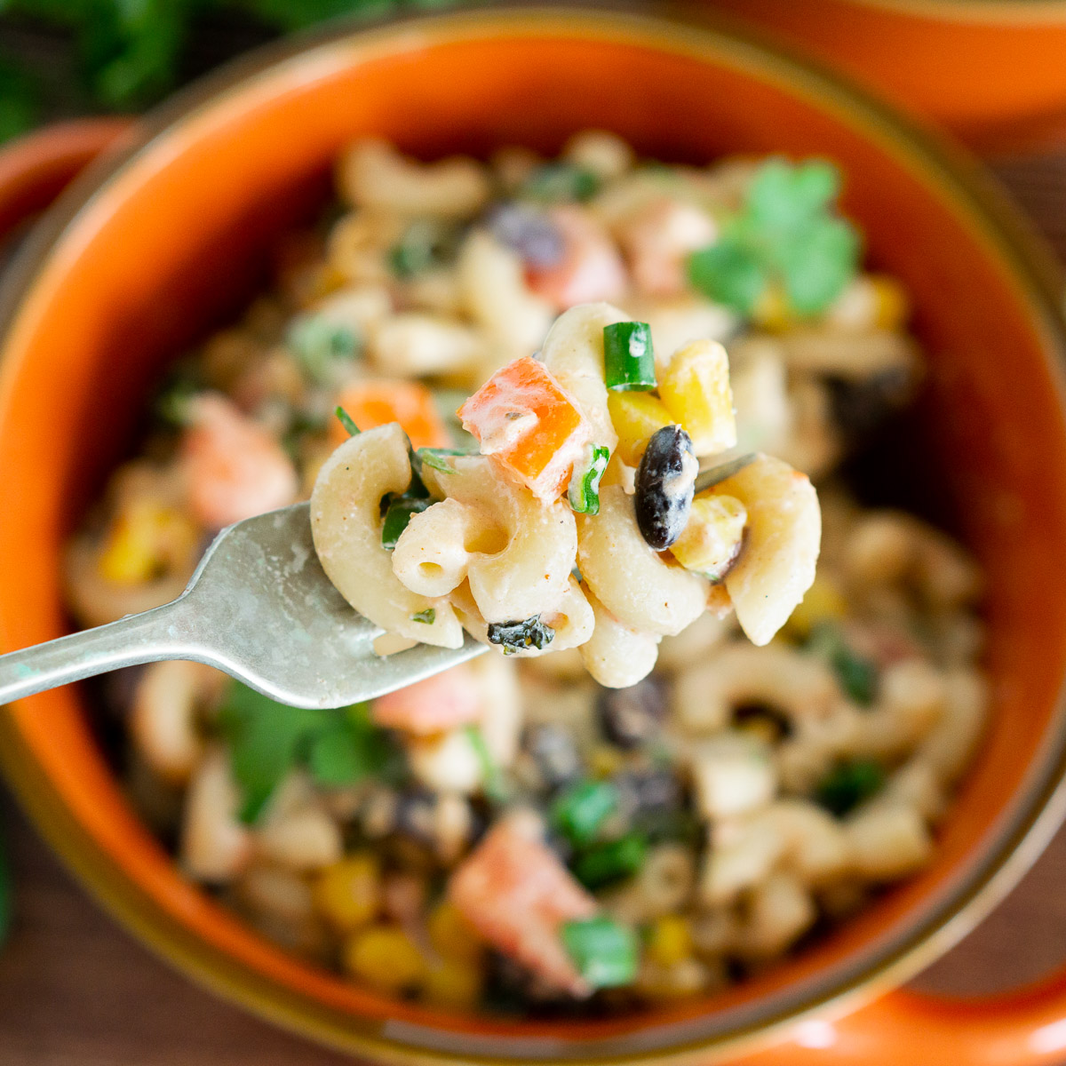 mexican macaroni salad with black beans on a fork