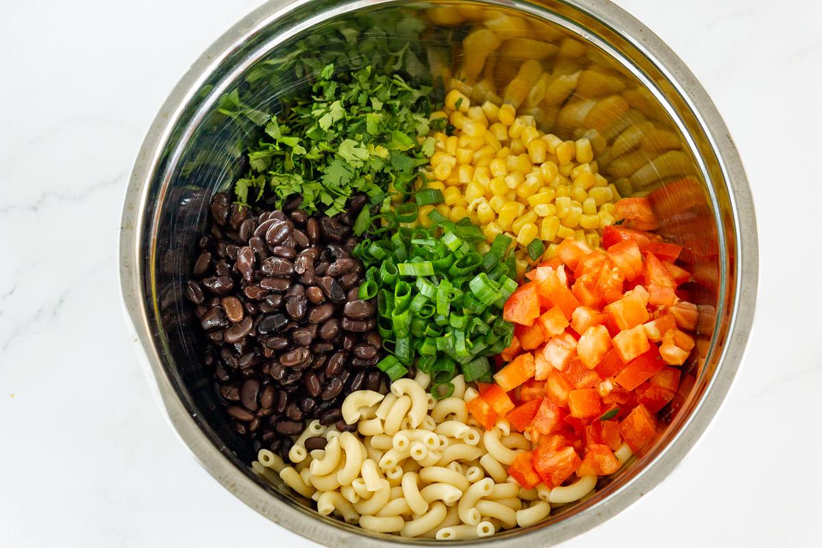 ingredients for mexican macaroni salad in a bowl: corn, black beans, tomato, cilantro, macaroni