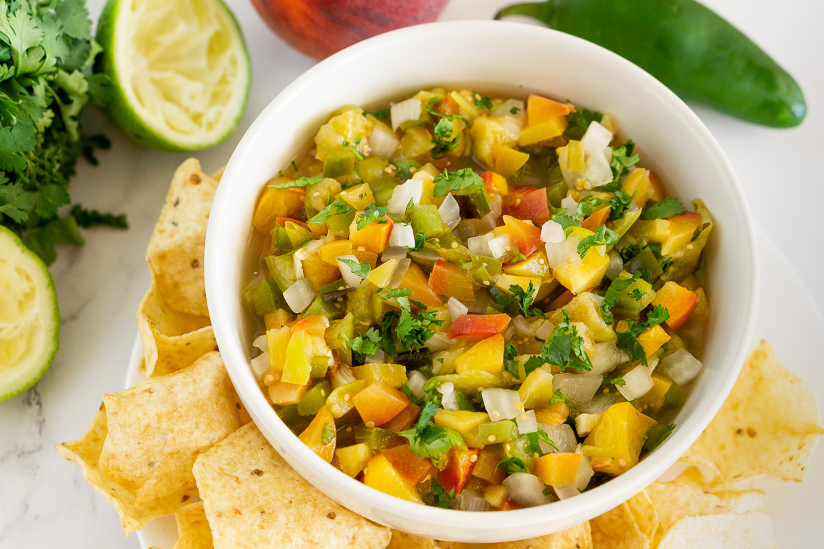 roasted peach tomatillo salsa in a bowl with tortilla chips