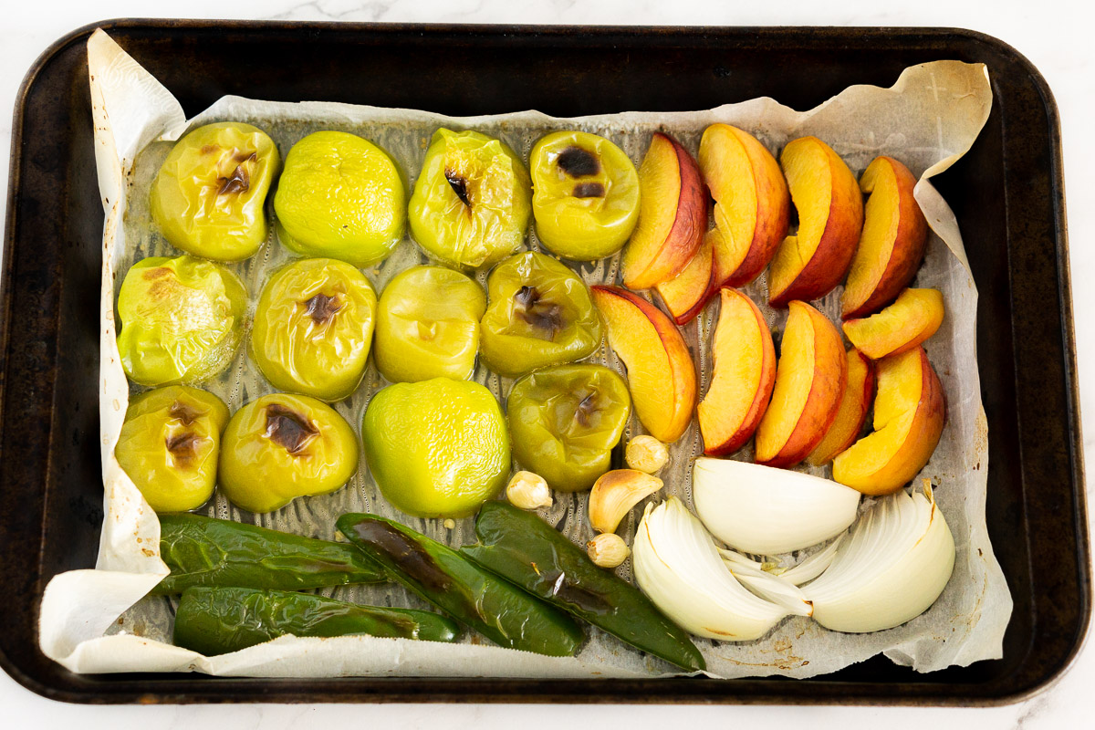roasted tomatillos, peaches, jalapenos, and onions in a baking sheet