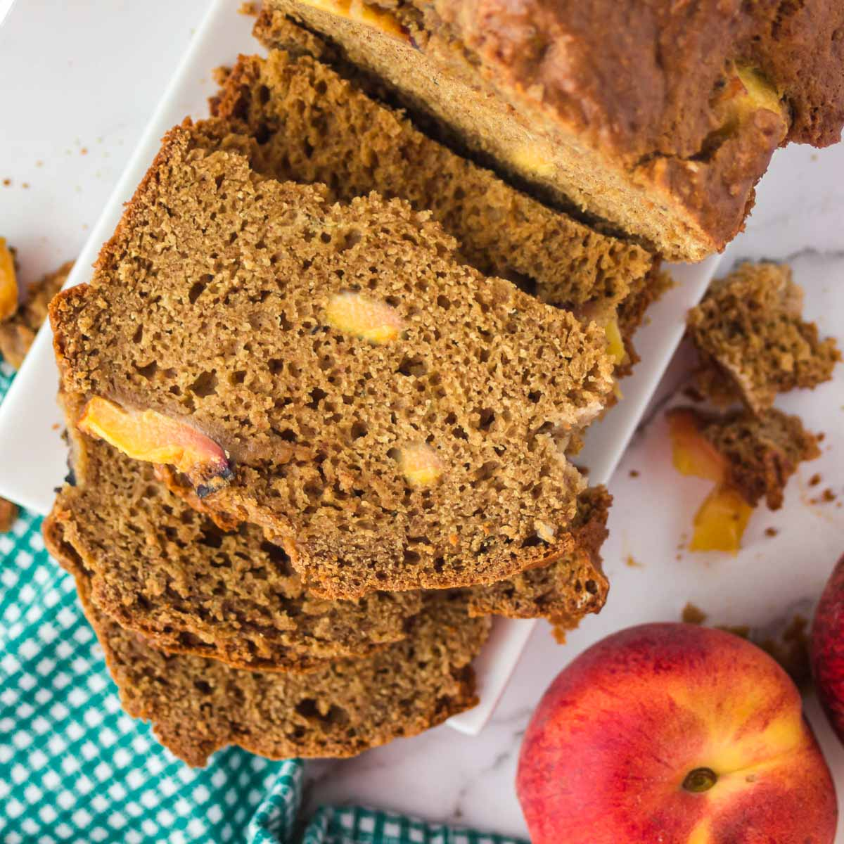 Sliced peach bread with fresh peaches.