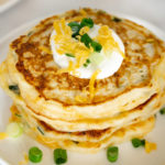 stack of savory pancakes with sour cream on top