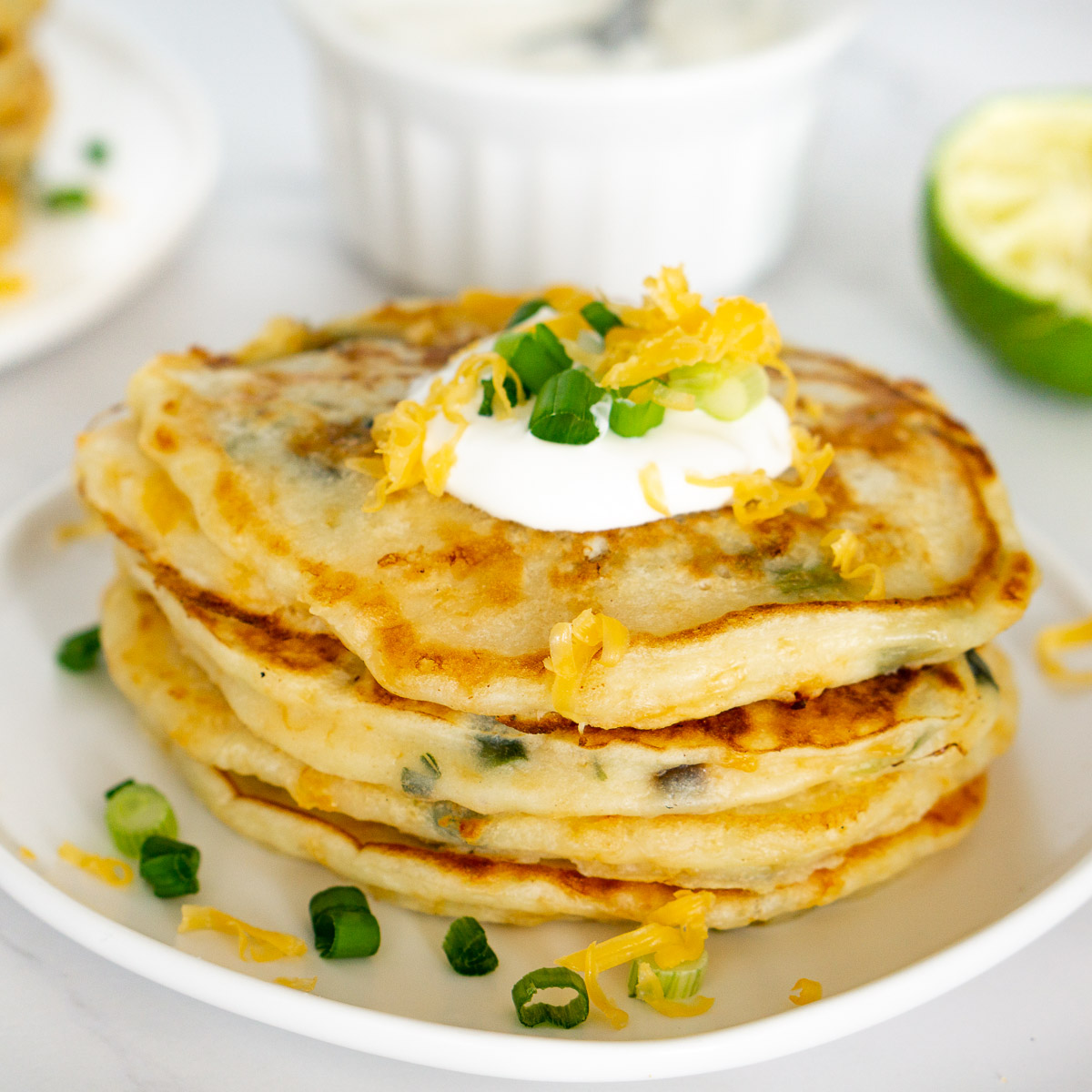stack of savory cheesy pancakes with scallions on a plate