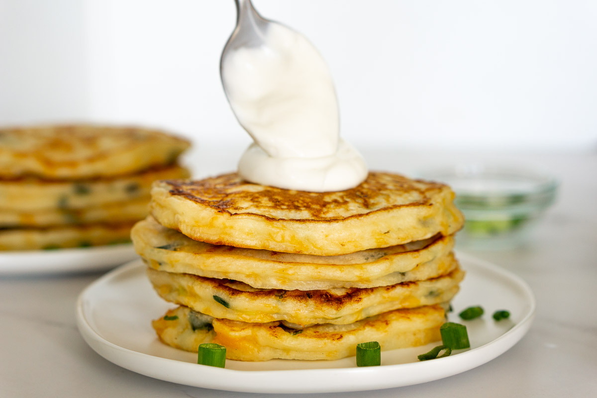 spooning lime crema onto a stack of savoury pancakes