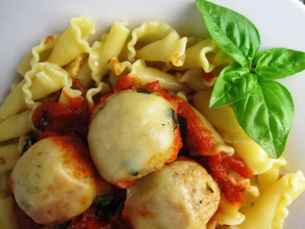 Cheesy Chicken Meatballs on a plate of pasta