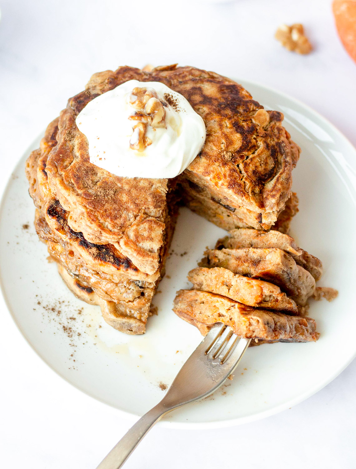 stack of carrot cake pancakes topped with vanilla Greek yogurt