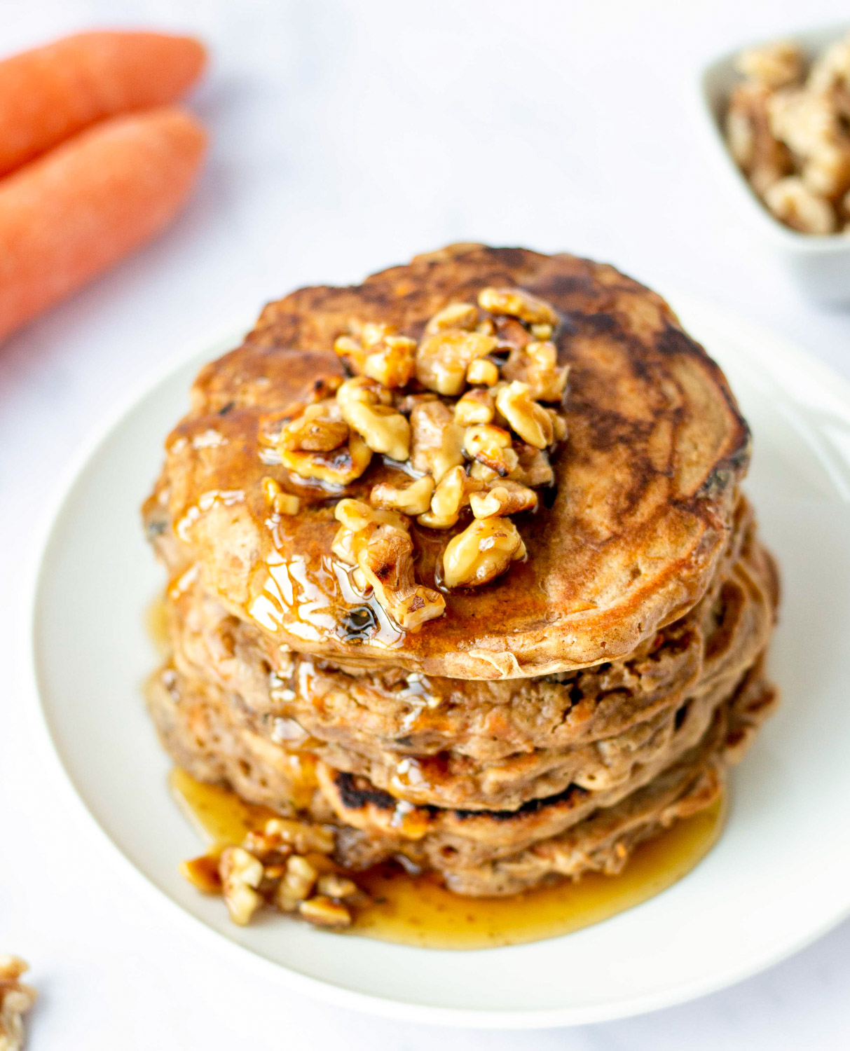 stack of carrot cake pancakes topped with walnut syrup and a carrot in the background
