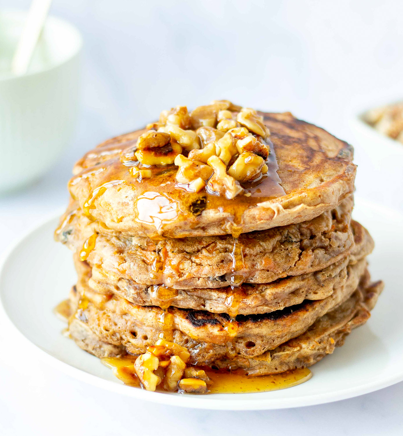 stack of whole wheat carrot cake pancakes topped with walnut syrup