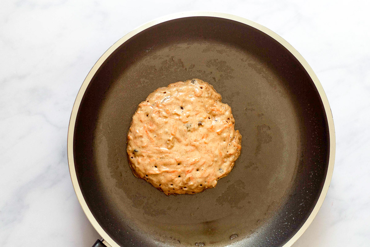 healthy carrot cake pancake cooking in a skillet