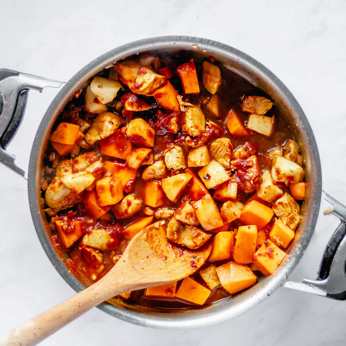 a spoon stirring pumpkin stew in a pot