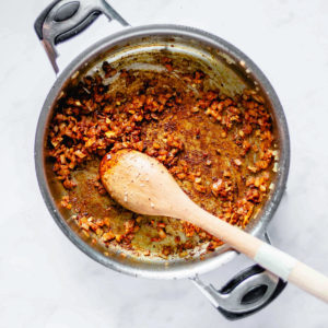 sauteing Moroccan spices with onion, ginger, and garlic in a pot
