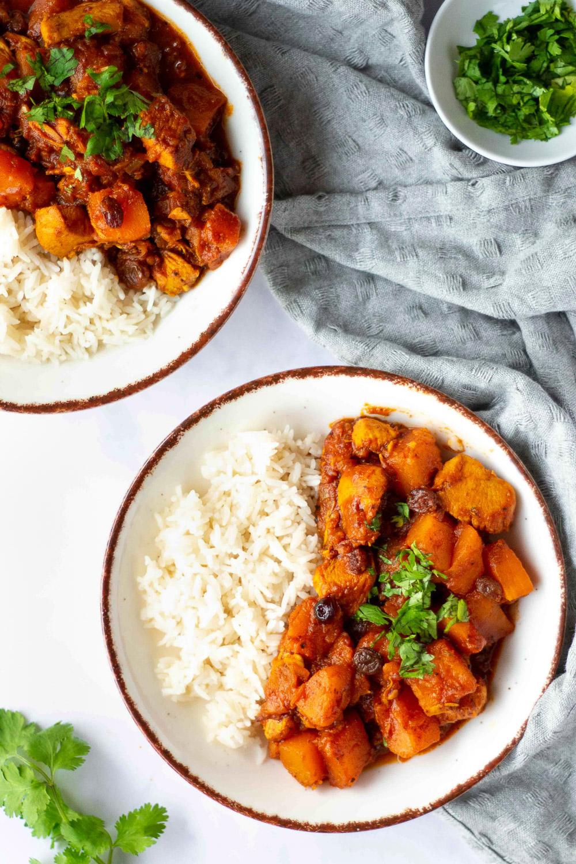 chicken pumpkin stew over rice on two plates