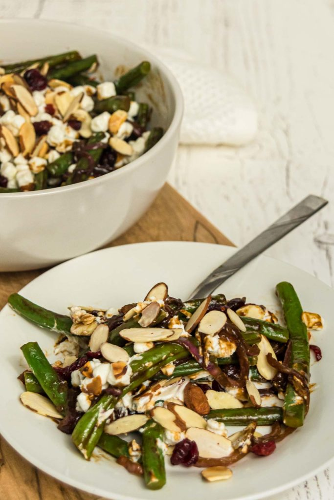 Plate of green beans with almonds, cranberries, and balsamic sauce.