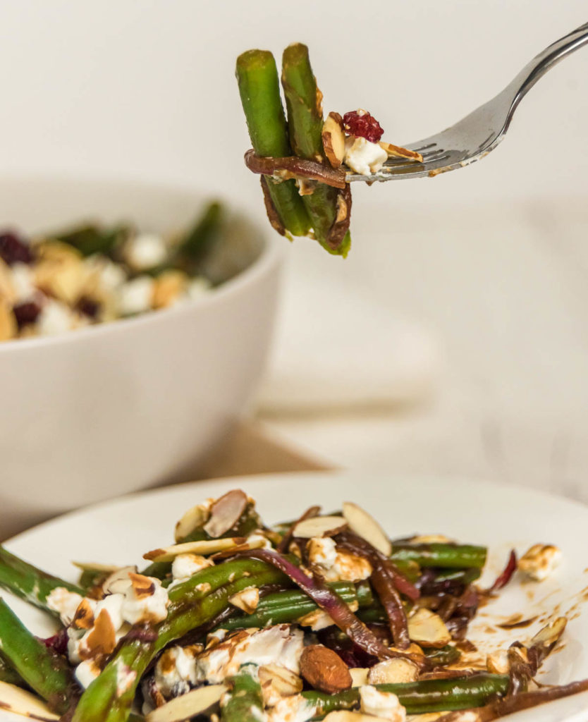 Fork picking up green beans with almonds and goat cheese.