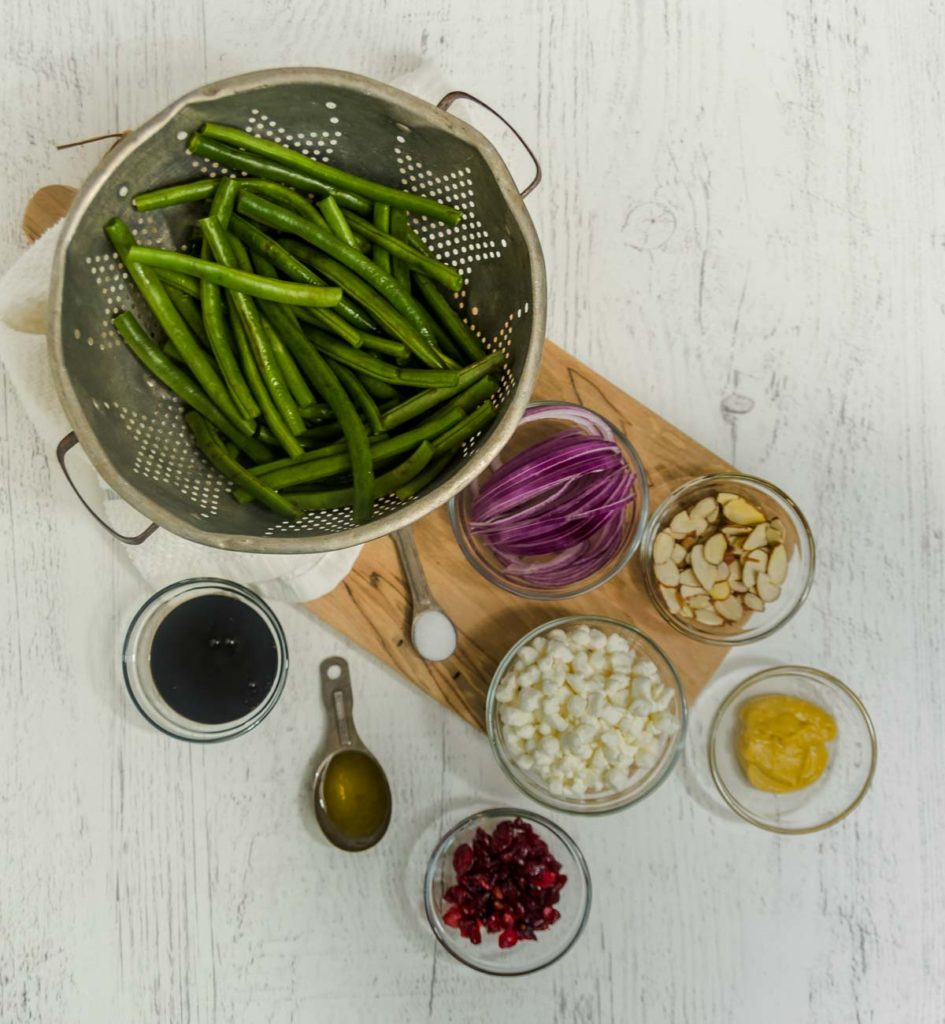 Ingredients to make green bean side dish: Green beans, balsamic glaze, Dijon mustard, red onions, craisins, almonds, and goat cheese.