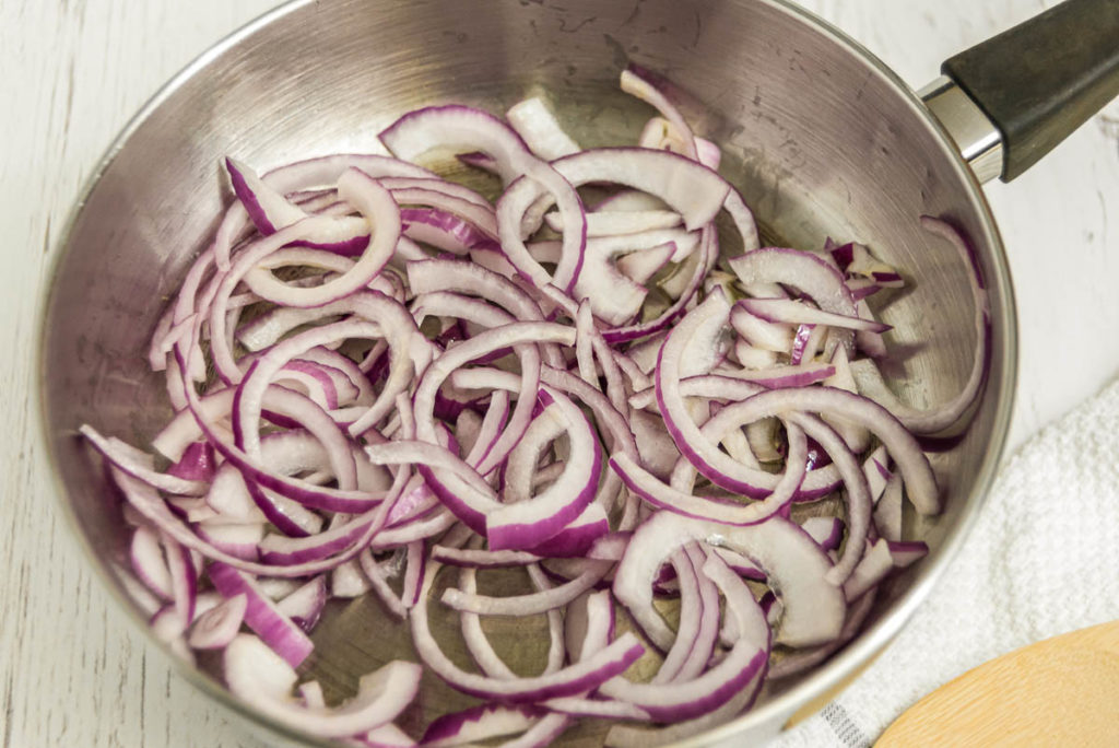 Sauteing sliced red onion.