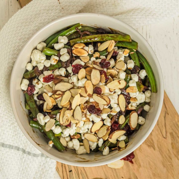 Bowl of green bean side dish with cranberries, almonds, and goat cheese.