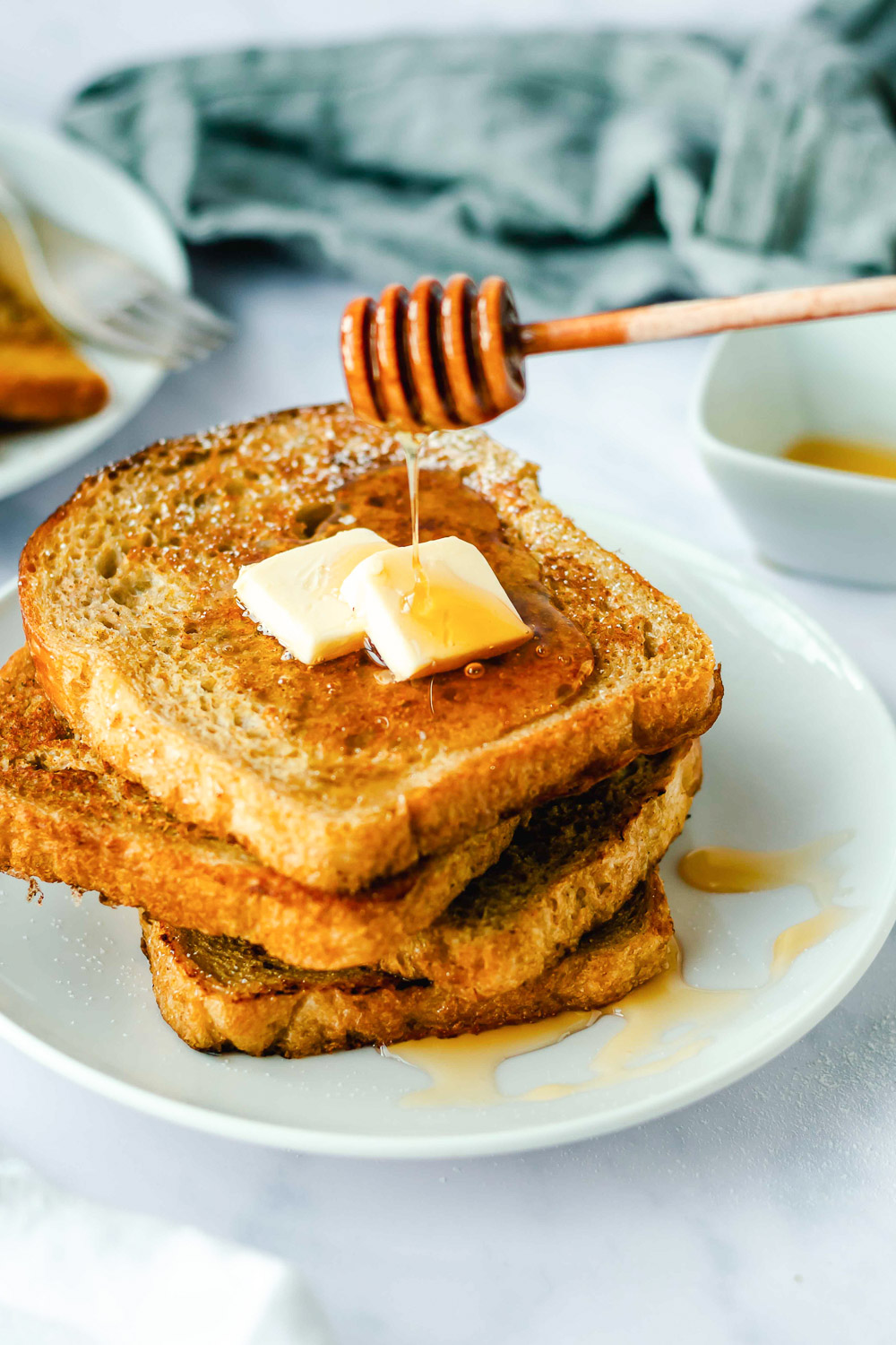 honey dripping onto a plate of Pumpkin French Toast topped with butter