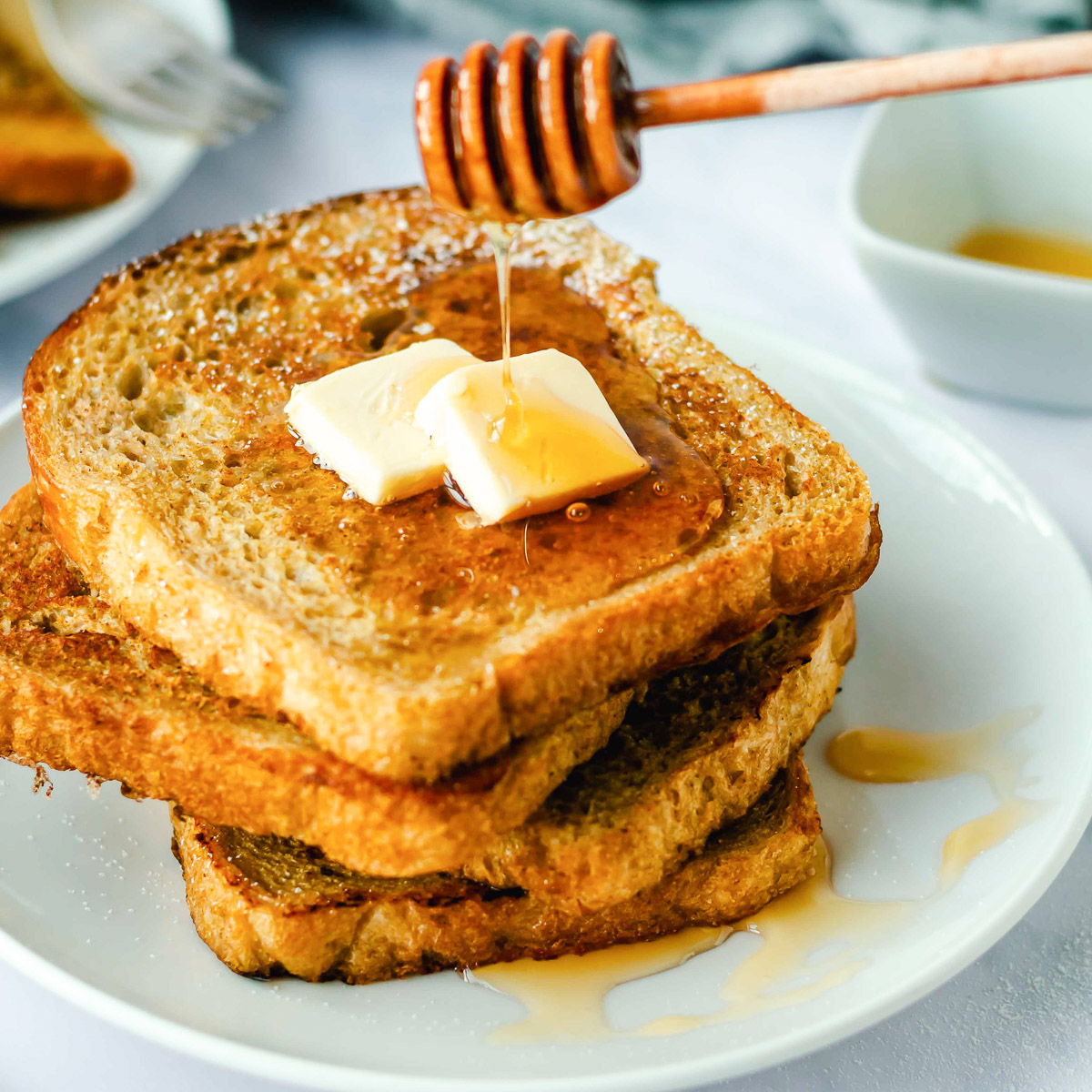 dripping honey onto a stack of pumpkin French toast