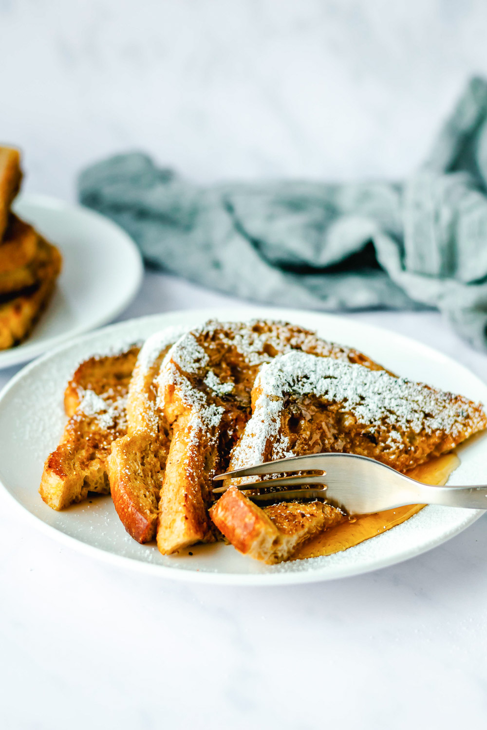 fork scooping up pumpkin french toast covered with powdered sugar