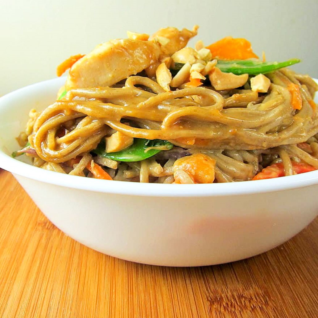 soba noodles with chicken, veggies, and peanut sauce in a bowl