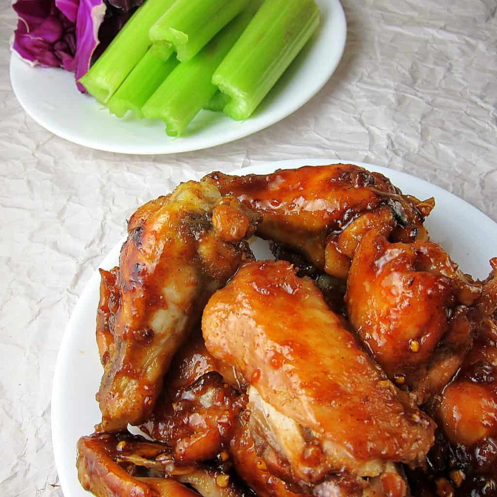 honey garlic ginger wings on a plate with celery in the background