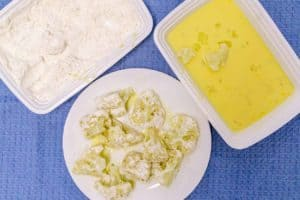 dipping cauliflower florets into the egg and flour mixture