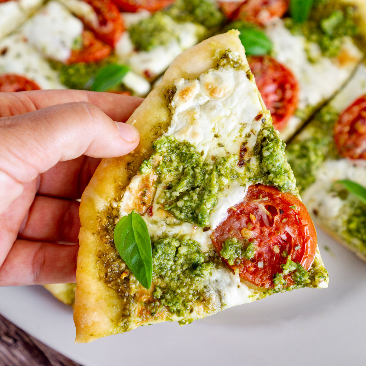 slice of pesto pizza made with 2 ingredient pizza dough
