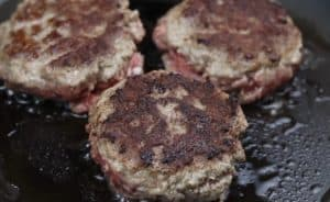 image of cooking venison burger patties on a skillet