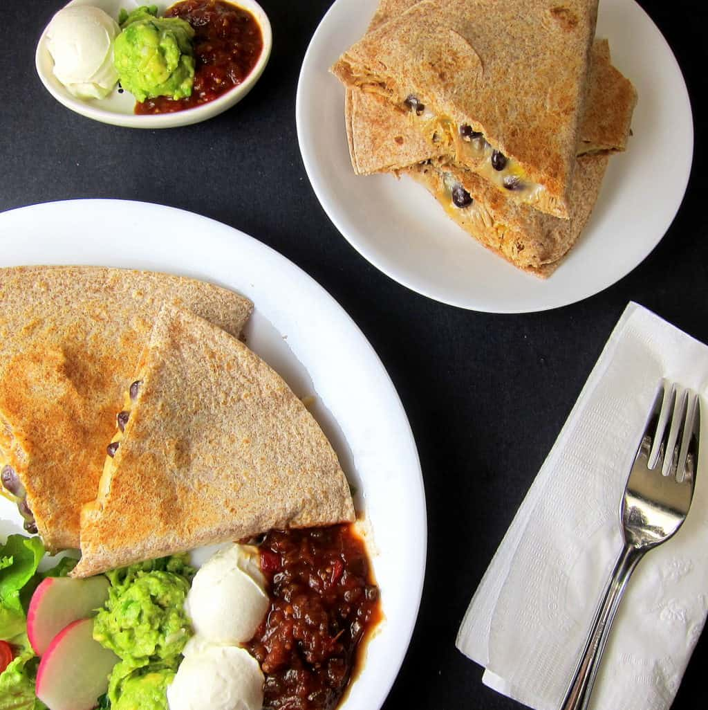 black bean pulled pork quesadilla on a plate with sour cream, guacamole, and salsa