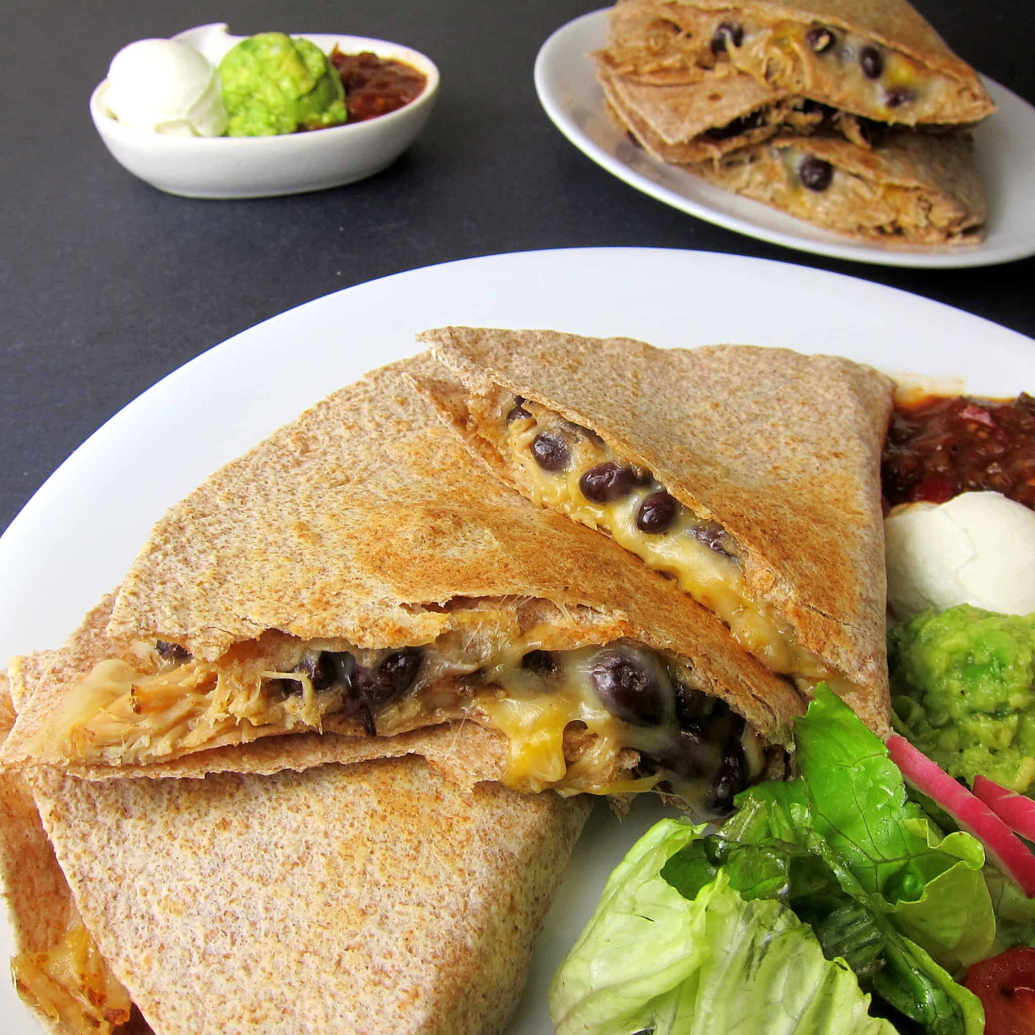 black bean pulled pork quesadilla on a plate with salad