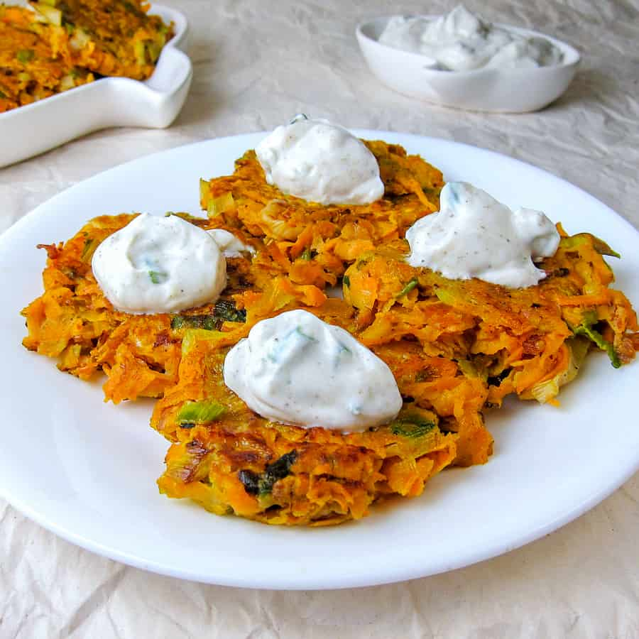 leek and sweet potato latkes on a plate with garlicky yogurt sauce
