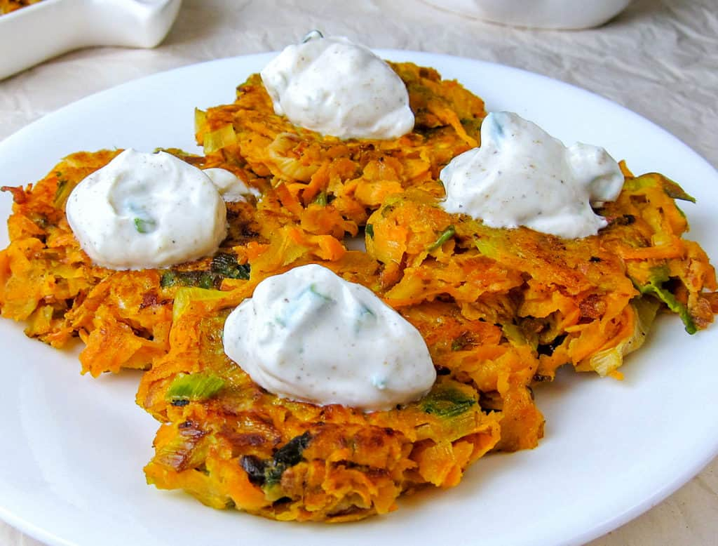 leek and sweet potato latkes topped with yogurt sauce