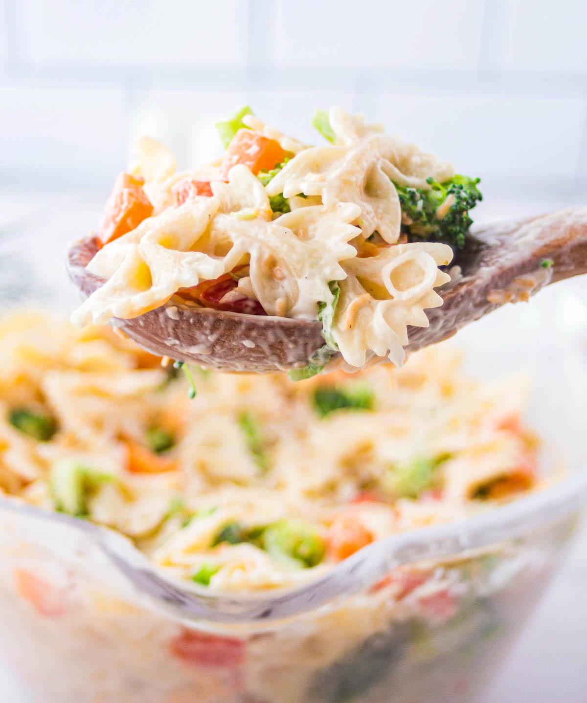 Broccoli ranch pasta salad on a serving spoon.