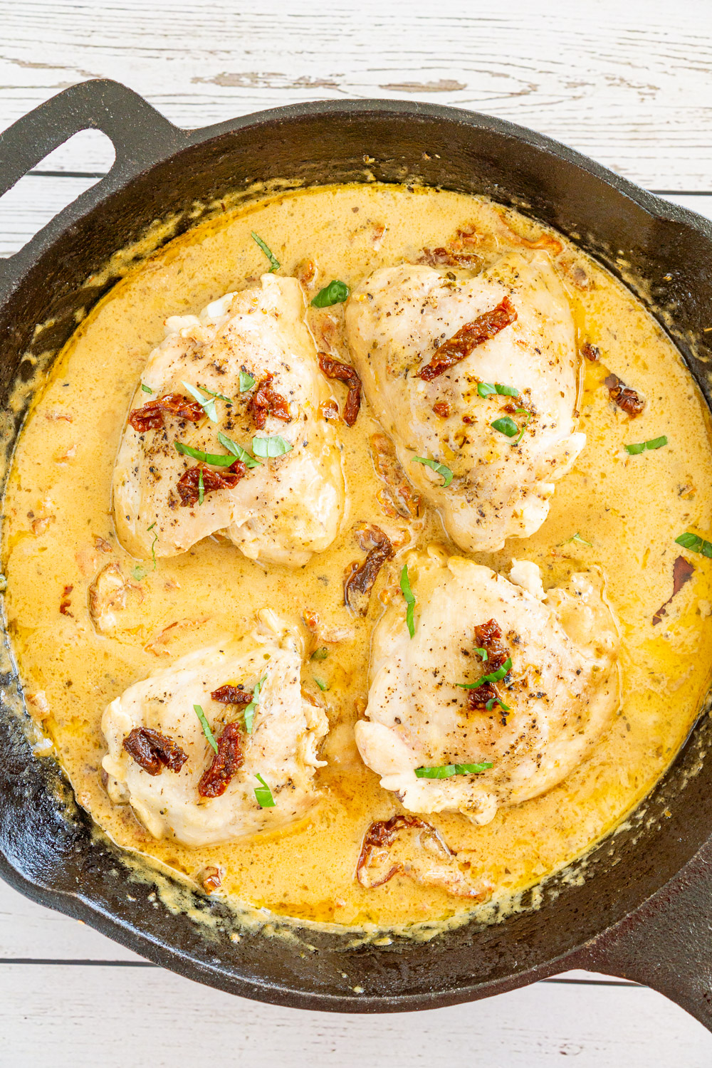 creamy sun dried tomato chicken thighs in a skillet