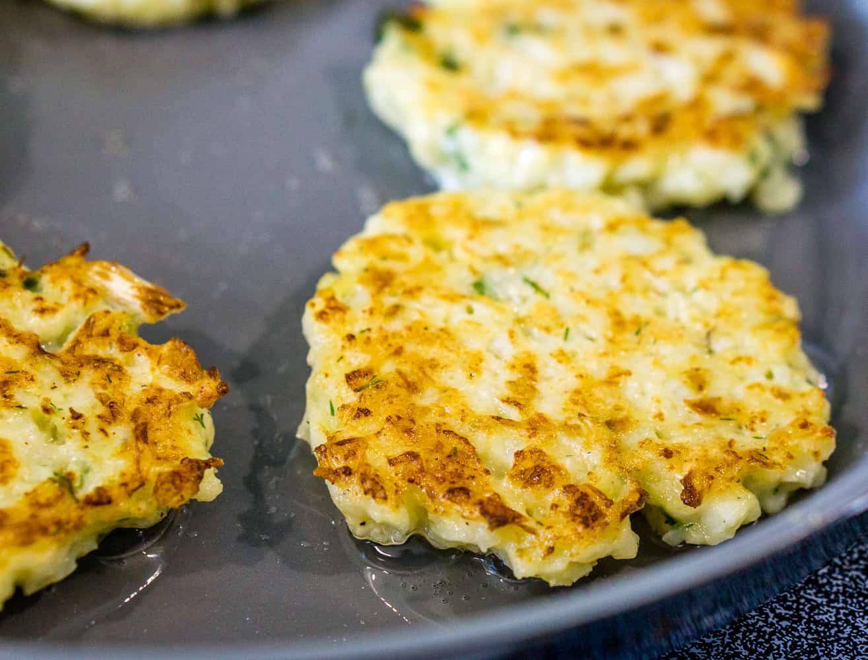 image of cauliflower pancakes in a frying pan