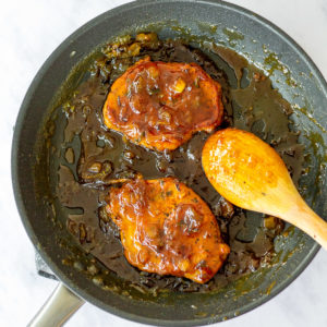 porkchops with pineapple sauce cooking in a pan