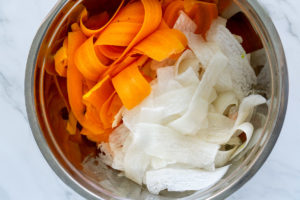 shaved carrot and shaved daikon radish in a bowl