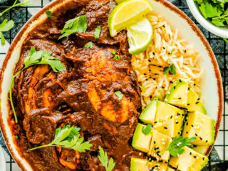 plate of chicken with mole sauce with rice and avocado