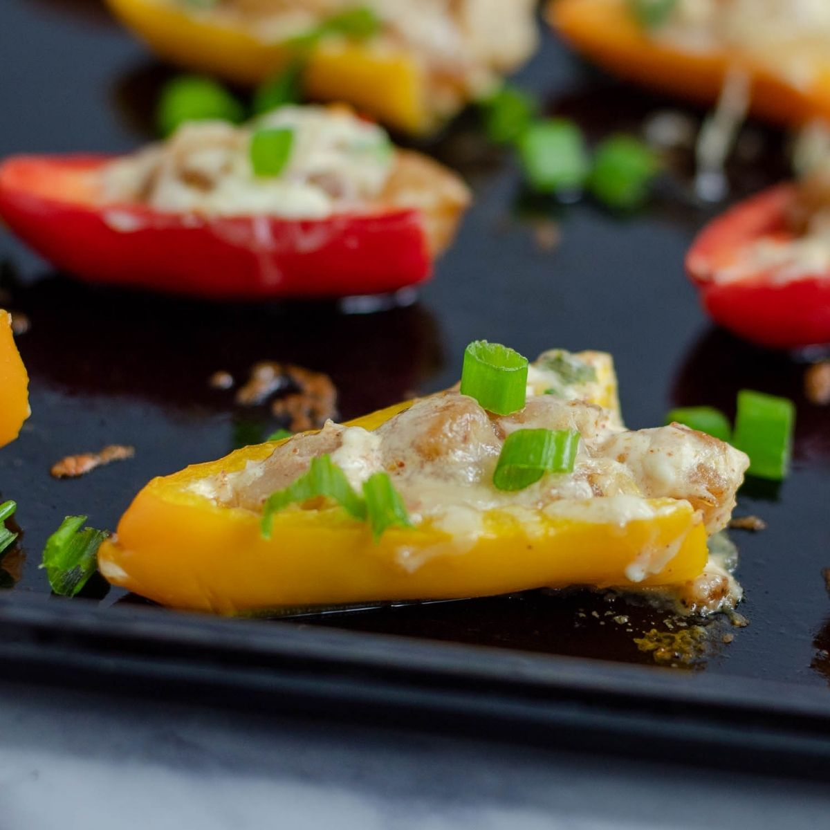 shrimp stuffed mini pepper topped with cheese on a baking tray