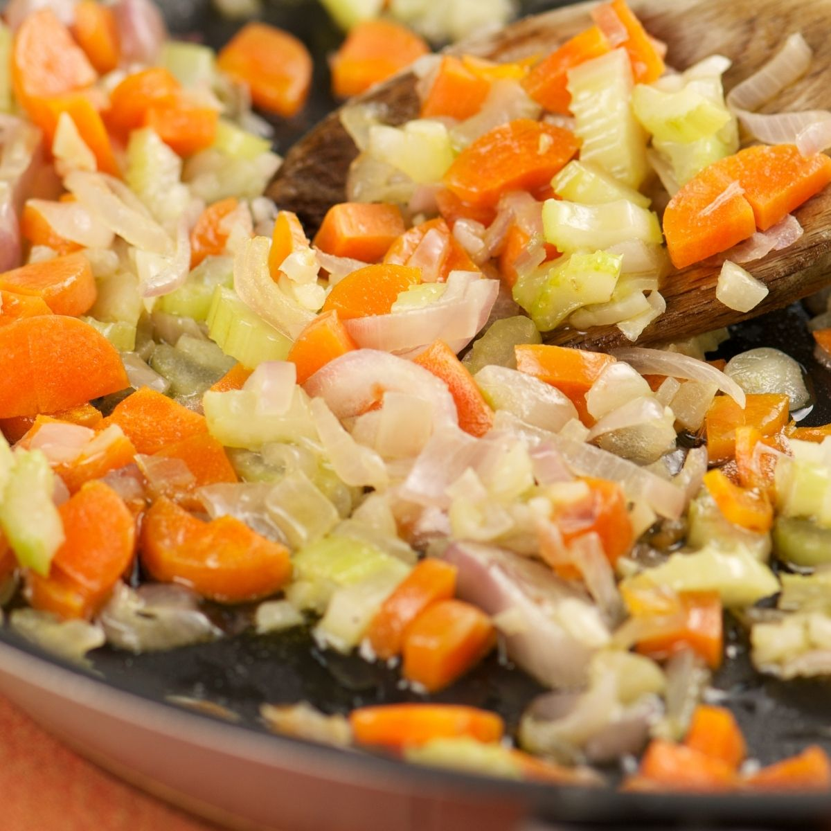 Sautéing carrots, onion, and celery in a pan.