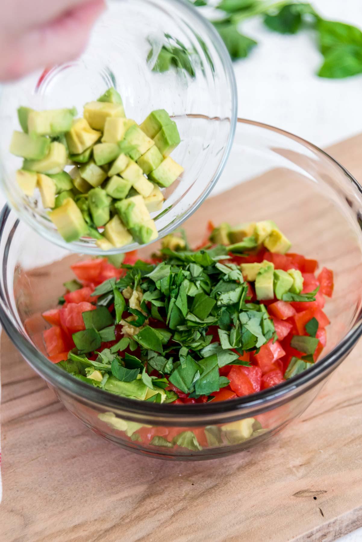 Adding diced avocado to tomato bruschetta in a bowl.