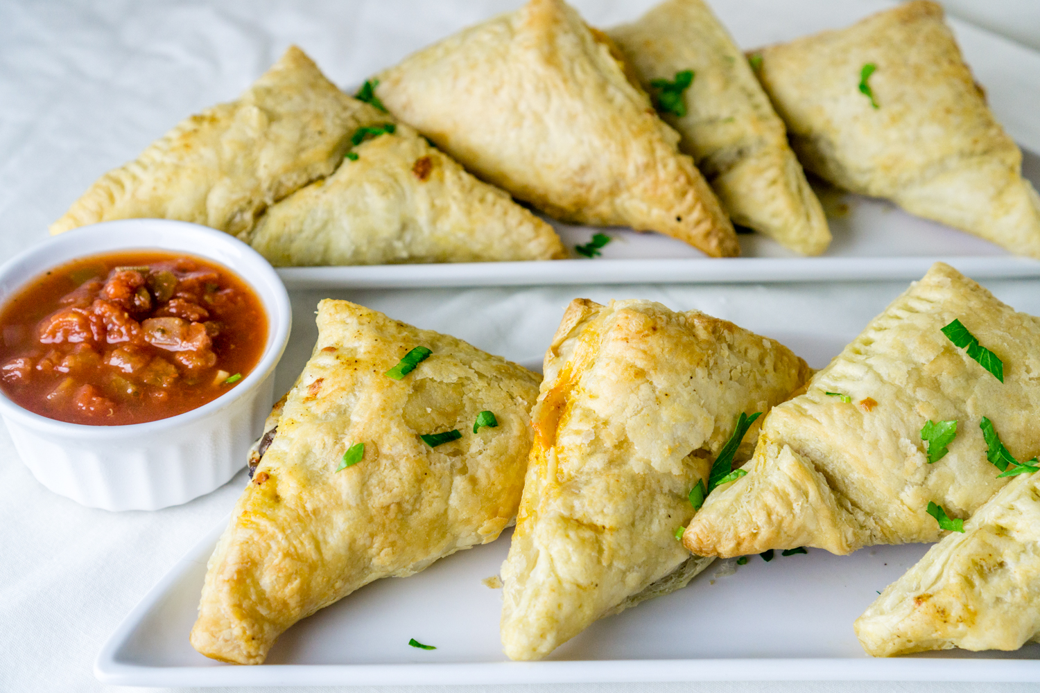 black bean puff pastry triangles with marinara sauce on serving plates