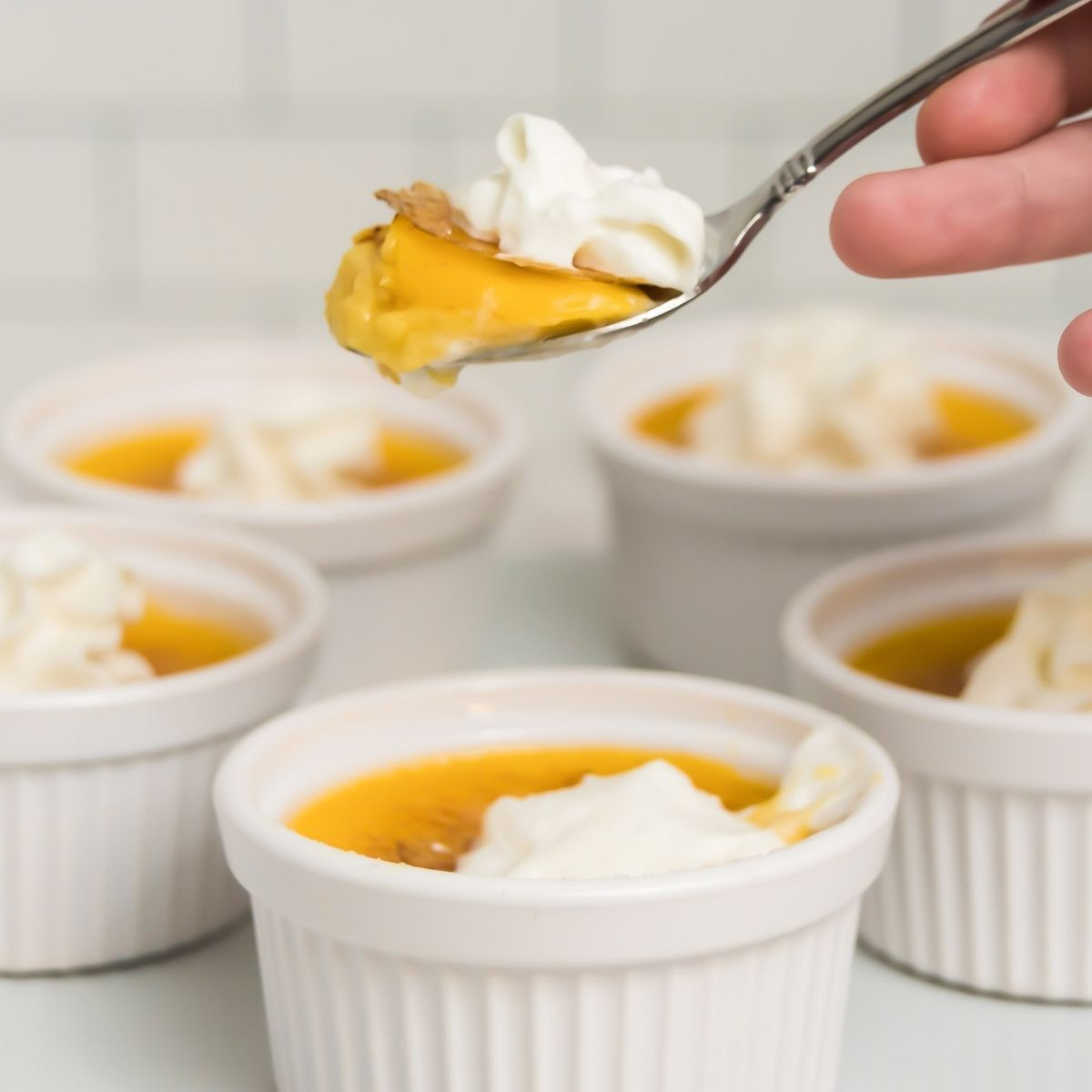 spoon holding creme brulee with whipped cream