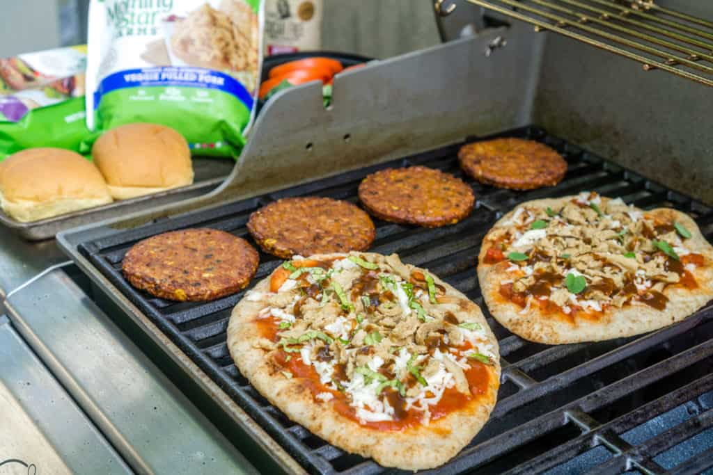 grilled naan pizza and grilled veggie burgers on a grill