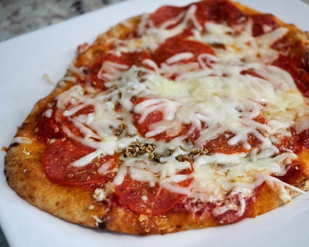 grilled naan pizza with pepperoni on a plate