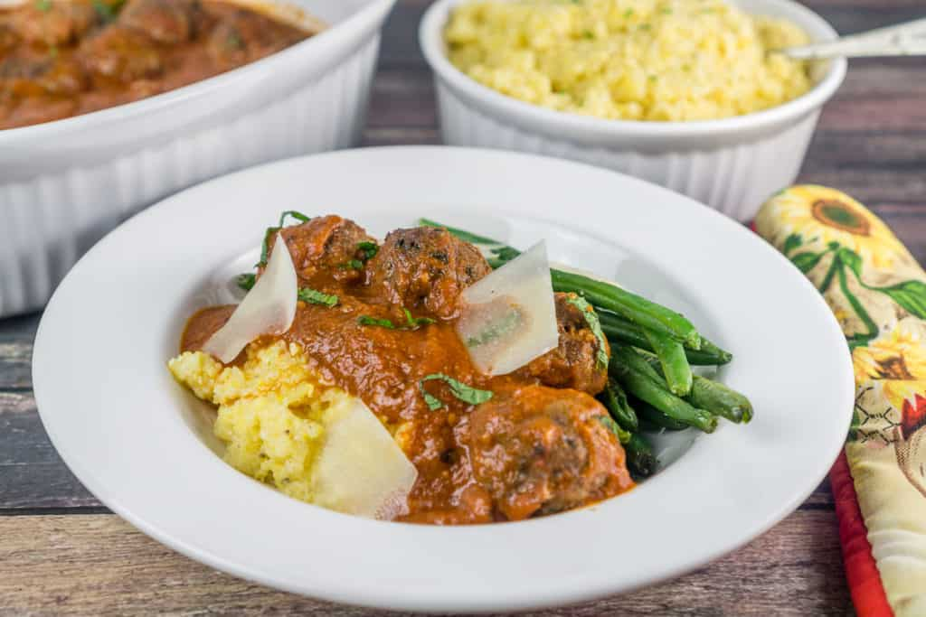 Dinner plate of Moroccan Meatballs with Polenta and Green Beans with Casserole dishes in the background | Babaganosh.org